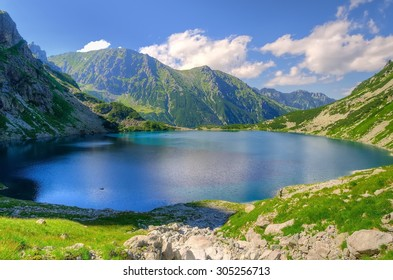 Summer mountain landscape. Beautiful lake in mountains. Czarny Staw (Black Pond) under Rysy, lake is the most popular place in High Tatra Mountains, Poland.