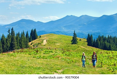 Summer mountain plateau landscape with dirty road and family walking