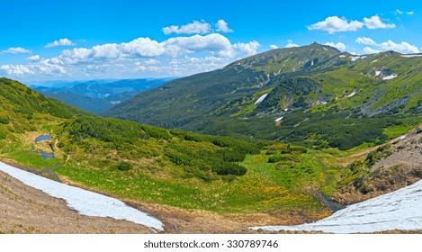 Summer mountain view with snow on mountainside (with observatory ruins on Chornogora Ridge, Ukraine).