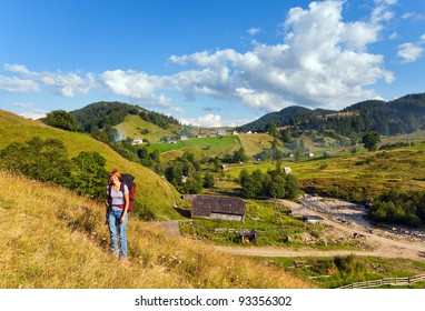Summer mountain village landscape and woman with tripod  in front