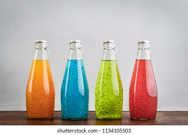 Summer multicolored refreshing drink in the bottles with basil seed and fruit juice on blue background. Exotic healthy beverage.