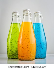 Summer multicolored refreshing drink in the bottles with basil seed and fruit juice on light background. Exotic healthy beverage.