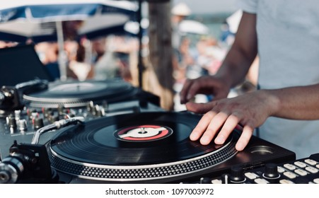 Summer music festival. DJ plays vinyl records, side view. Blurred crowd of raving funs on the background.