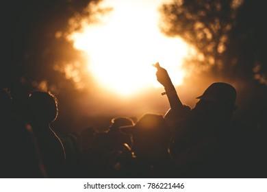 Summer music festival sunset, people silhouette.