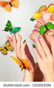 Summer nail design with stickers from butterflies. Beautiful smiling girl in glasses.
