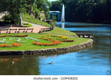 "Summer National Dendrology Park of Sofiyivka, Fountain ""Snake"", lake and flowerbed on lawn. Uman, Ukraine. Build in 19th century. People unrecognizable."