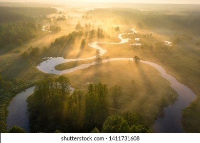 Summer nature landscape aerial view. Foggy morning river in sunlight. Sunny riverside from above. Amazing nature scene at misty sunrise. Bright sun shines on grassy meadow with river
