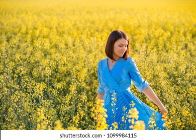 Summer nature. Young woman in blue dress walking on yellow field in the evening. Attractive girl outdoors enjoying fresh air. Allergy free theme.