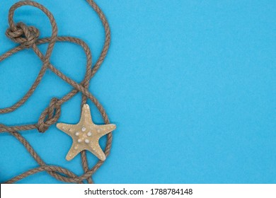 Summer nautical composition, starfish and knot woven from a rope on blue background