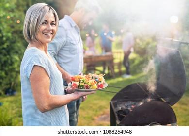 Im Sommer. Ein schönes Paar bereitet einen BBQ vor, um Freunde im Garten willkommen zu heißen. Sie hält einen Teller mit gegrillten Skewers