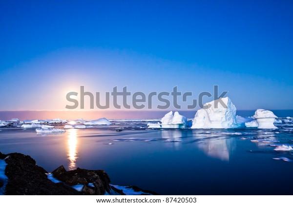 Summer night in Antarctica.Icebergs floating in the moonlight