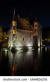 Summer night in the charming medieval town. Old fortress-prison on the island in the middle of the river. Castle illuminated by spotlights and is beautifully reflected in the dark water.