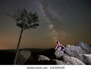 Summer night in mountains. Tall pine tree and slim tourist girl sitting alone with closed eyes on top of huge boulder, doing yoga on clear starry sky background. Healthy lifestyle concept. Siddhasana