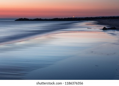 Summer night sunset beach colorful light on a danish beach at a calm evening with sky reflection on a wet sand.  Lønstrup in North Jutland in Denmark, Skagerrak, North Sea