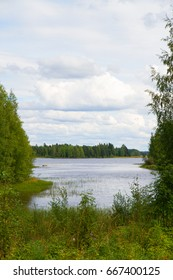 Summer nordic landscape with lake surrounded by forests. Vertical photo.