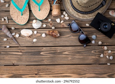 Summer objects among sea shells and stones on wooden background. Flip-flops, straw hat, sunglasses, photocamera are the must to take.