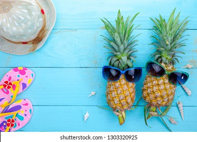 Summer objects of pineapple with sunglasses summer accessory on blue wooden background.