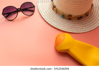 Summer objects with a pink background (straw hat, sunglasses and sunscreen). Tropical summer vacation concept. Top view. Flat lay