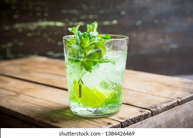 Summer old fashioned beverage with melon liqueur and mint leaves. Selective focus. Shallow depth of field.