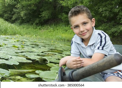 In the summer on the river curly little boy sitting on a rubber boat near water lilies.