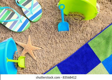 Summer on the Sand: Beach towel surrounded by color coordinated beach accessories and starfish suggest a summer beach vacation. Great background, stock, concept, vacation/recreation, and travel image.