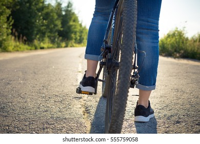 in the summer on a sunny day walk on the bike, the girl goes in for sports