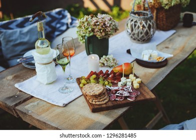 summer outdoor garden table setting with flowers, candles, white wine, cheese and fruits