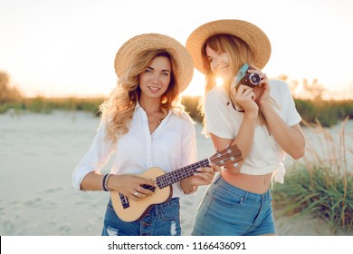 Summer outdoor image of two pretty travel women, cheerful friends enjoying holidays together in countryside . Playing ukulele guitar and making photos.