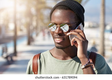Summer outdoor portrait of carefree relaxed black male student having phone conversation on his way to college. Fashionable dark-skinned guy talking on electronic gadget in urban surroundings