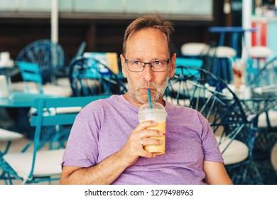Summer outdoor portrait of happy man holding milkshake