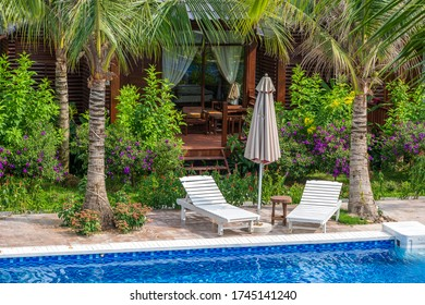 Summer outdoor swimming pool and sun loungers near sea on the tropical beach in Phu Quoc island, Vietnam, Southeast Asia. Concept of nature and the environment