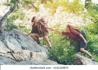 Summer Outdoors. Group Hiker woman helping her friend climb up the last section of sunset in mountains. Traveler teamwork walking in outdoor lifestyle adventure and camping. Travel Concept.