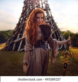 Summer outdoors portrait of beautiful furious scandinavian warrior ginger woman in a traditional clothes with fur collar, with sword in her hand and wooden Nikola-Lenivets view on the background.