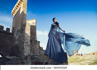 Summer outdoors portrait of beautiful furious scandinavian warrior ginger woman in grey dress with metal chain mail. Fortress Sudak, Crimea