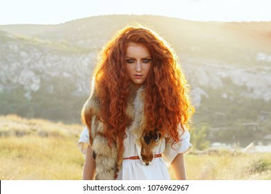 Summer outdoors portrait of beautiful scandinavian warrior viking redhead woman in a traditional historical clothes and landscape view on the background. Girl is looking at the camera.