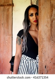 Summer Outfit - Beautiful african italian woman with granny hairstyle, black body, black and white striped pants, black high heels shoes, black leather bag, near an abandoned and ruined house.