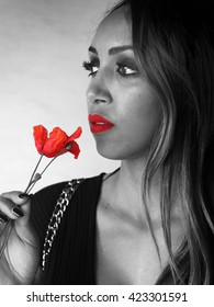 Summer Outfit - Black and white portrait of a beautiful african italian woman with red lips, handling a poppy