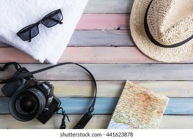 Summer outfit and objects. Vacation concept. Sunglasses, towels, straw hat, camera and map on vintage background.