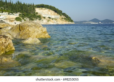 Summer panorama of azure sea and green mountains