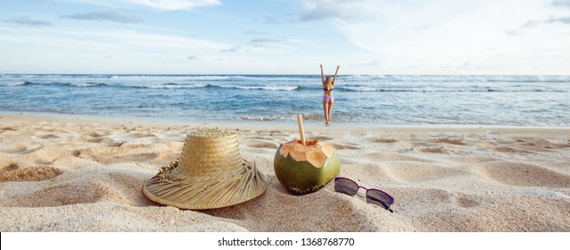 Summer panorama. The girl walks on the beach in defocus. Coconut, hat and sunglasses lie on the sand, closeup.