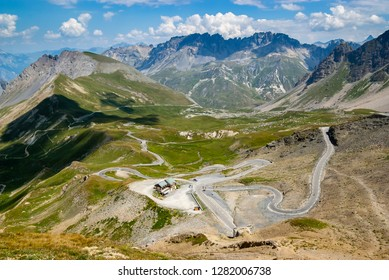 Summer panorama from the top of a mountain pass Col du Galibier. Alpine serpentine road, winding in a green alpine valley surrounded by impressive high mountains, French Alps.
