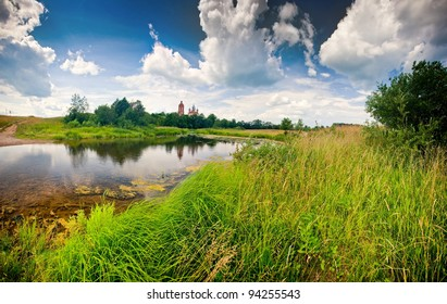 Summer panoramic landscape with river and church