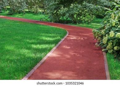 Summer Park With A Red Pedestrian Gravel Walkway Or Footpath. Modern Garden  Landscaping. Garden