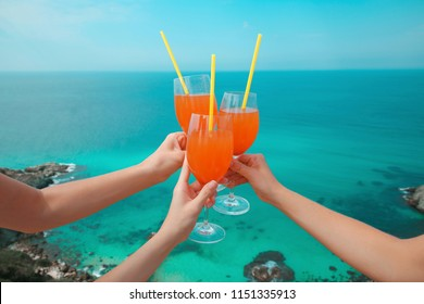 Summer party Cheers! Cropped image Hands of three people holding orange coctail glass with Straw over turquoise lagoon exotic bay. Lifestyle summer vacations concept. Black sea coast, Crimea.