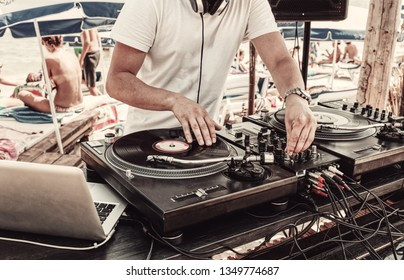 Summer party - dj's hands and sound equipment. Dj plays vinyl record and turns equalizer on mixer
