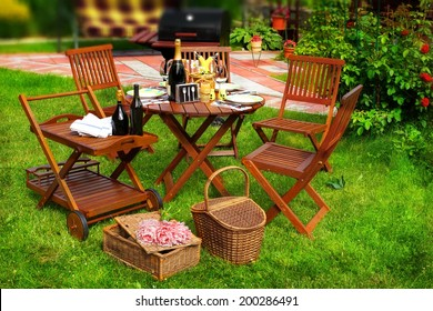 Summer Party or Picnic Scene. Outdoor furniture on the lawn. BBQ Grill in blurred background.