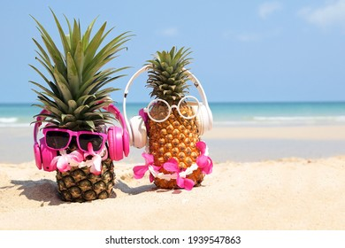 Summer party. Pineapple wearing sunglasses and listen to music on beach and blue sky background. Tropical fashion. Summer Fashion on holiday concept.