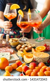 Summer party: three girls are having Aperol Spritz coktails served with ice in wine glasses, decorated with orange slices. Extremely bright colors. Fresh fruits is accompaniment. Atmosphere of joy