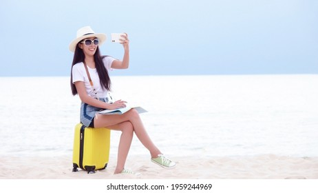 Summer Party. Traveler and tourism woman travel in summer on the beach and white sand. Asian is taking photos and sitting on yellow suitcase for travel tripr. Summer Vacation