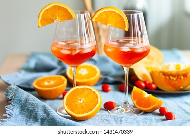 Summer party: two cocktails  Aperol Spritz are served with ice in wine glasses, decorated with orange slices. Blue contrast background, extremely bright colors. Fresh fruits is accompaniment.